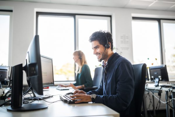 Side view of smiling customer service representative wearing headset using computer while sitting by colleague at brightly lit office
